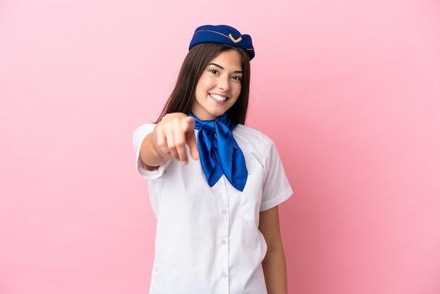 분홍색 배경에 격리된 비행기 스튜어디스 브라질 여성은 자신감 있는 표정으로 당신을 손가락으로 가리킵니다.