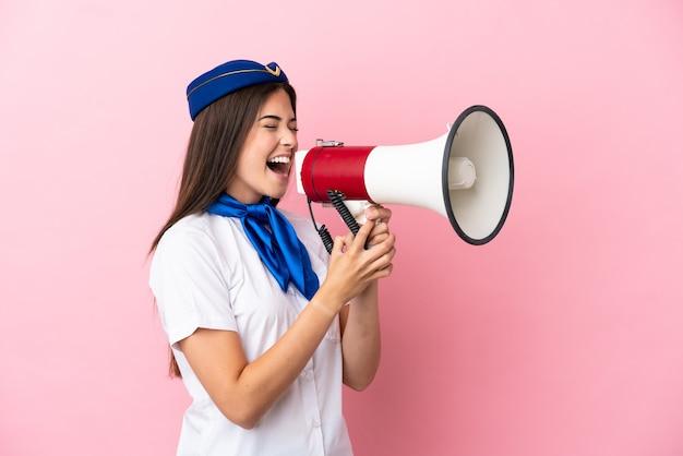 Стюардесса самолета бразильская женщина изолирована на розовом фоне кричит через мегафон
