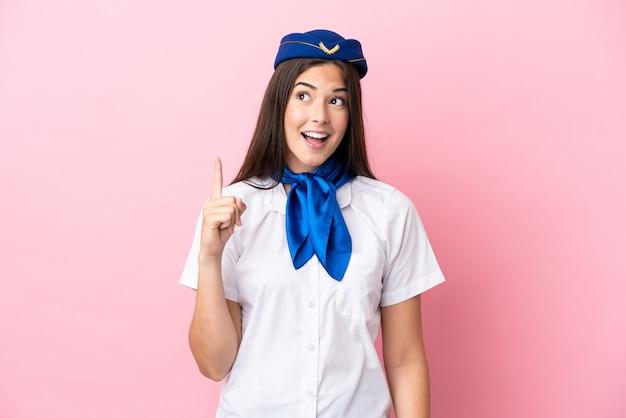Бразильская женщина-стюардесса изолирована на розовом фоне, думая, что идея указывает пальцем вверх