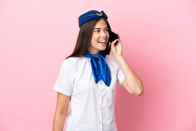 Airplane stewardess brazilian woman isolated on pink background keeping a conversation with the mobile phone