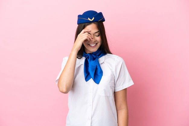 Airplane stewardess brazilian woman isolated on pink background laughing
