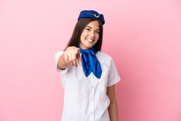 Airplane stewardess brazilian woman isolated on pink background points finger at you with a confident expression