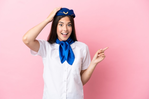 Airplane stewardess brazilian woman isolated on pink background surprised and pointing finger to the side