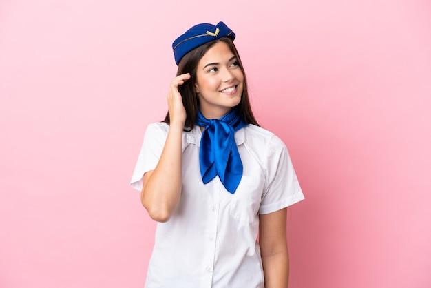 Airplane stewardess brazilian woman isolated on pink background thinking an idea