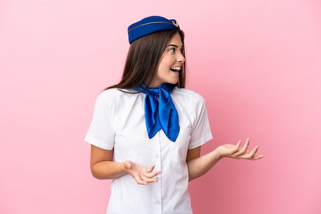 Airplane stewardess brazilian woman isolated on pink background with surprise facial expression