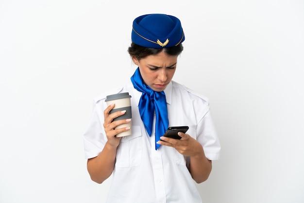 Стюардесса самолета кавказская женщина, изолированные на белом фоне, держа кофе на вынос и мобильный