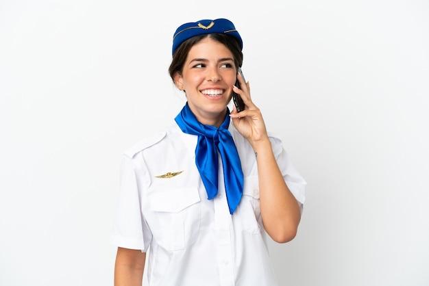 비행기 스튜어디스 백인 여자는 휴대 전화와 대화를 유지 하는 흰색 배경에 고립