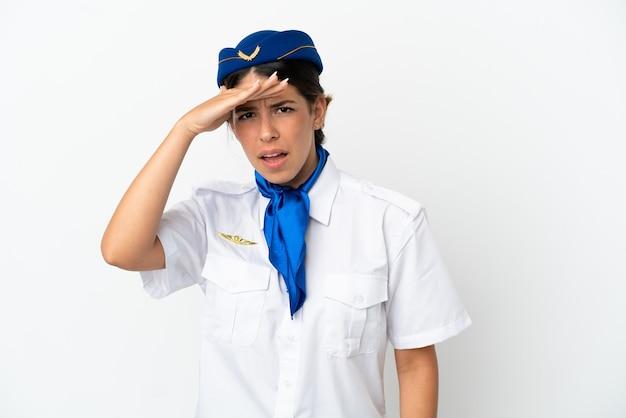 흰색 배경에 고립 된 비행기 스튜어디스 백인 여자 손으로 멀리보고 뭔가를 찾고