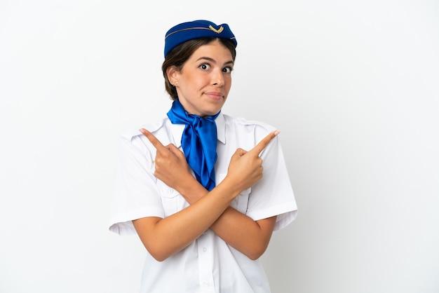 흰색 배경에 격리된 비행기 스튜어디스 백인 여성이 의심스러운 측면을 가리키고 있습니다.