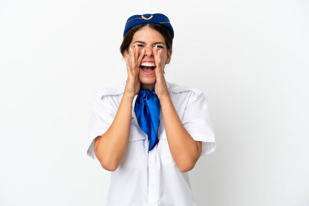 흰색 배경에 격리된 비행기 스튜어디스 백인 여성이 소리를 지르며 무언가를 발표합니다.