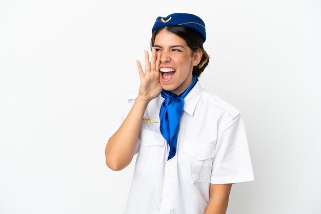 飛行機のスチュワーデス白人女性が白い背景で隔離の口を横に大きく開いて叫んでいる