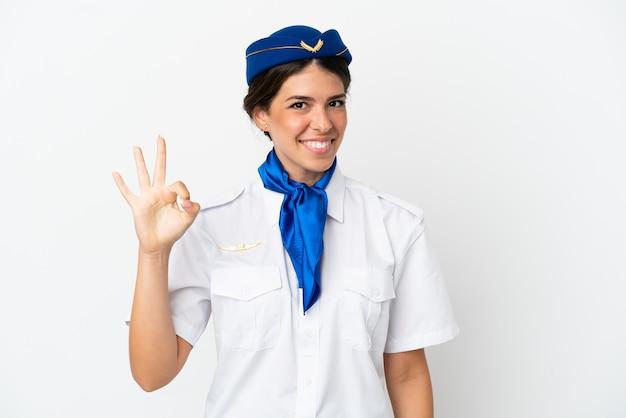 흰색 배경에 격리된 비행기 스튜어디스 백인 여성이 손가락으로 확인 표시를 하고 있습니다.
