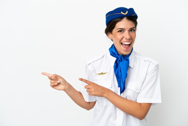 흰색 배경에 고립 된 비행기 스튜어디스 백인 여성 놀라고 가리키는 쪽