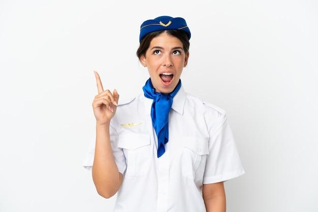 흰색 배경에 격리된 비행기 스튜어디스 백인 여성이 손가락을 가리키는 아이디어를 생각하고 있습니다.