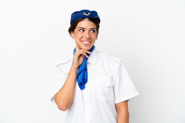 흰색 배경에 격리된 비행기 스튜어디스 백인 여성은 올려다보는 동안 아이디어를 생각하고 있습니다.