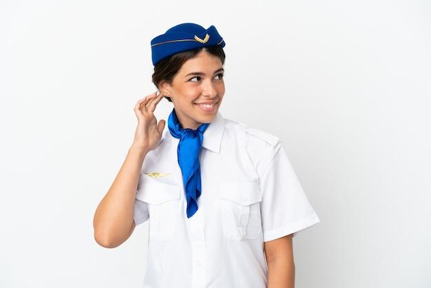 アイデアを考えて白い背景で隔離の飛行機スチュワーデス白人女性