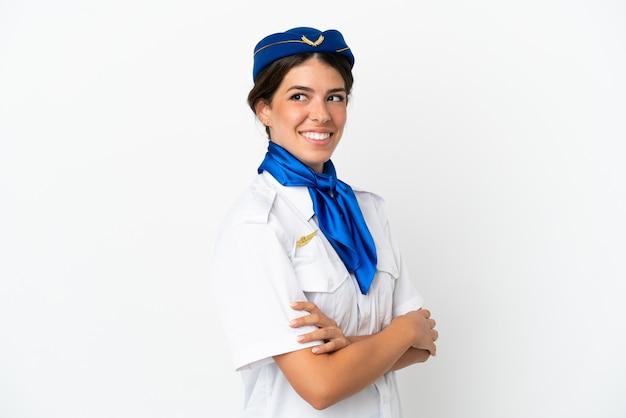 팔짱을 끼고 행복한 흰색 배경에 격리된 비행기 스튜어디스 백인 여성