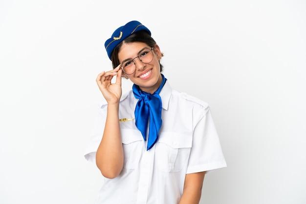 眼鏡と幸せな白い背景で隔離の飛行機スチュワーデス白人女性