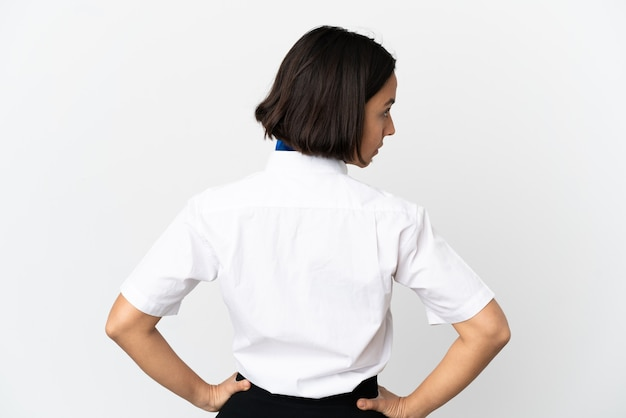 Airplane stewardess over isolated background in back position and looking side
