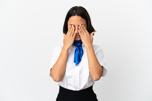 Airplane stewardess over isolated background covering eyes by hands