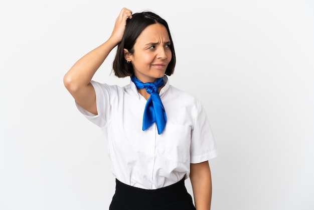 Airplane stewardess over isolated background having doubts while scratching head