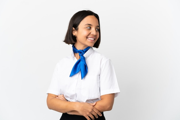 Airplane stewardess over isolated background looking to the side and smiling