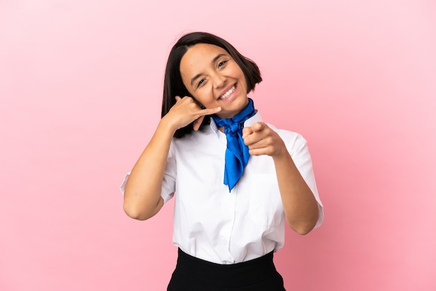 Airplane stewardess over isolated background making phone gesture and pointing front