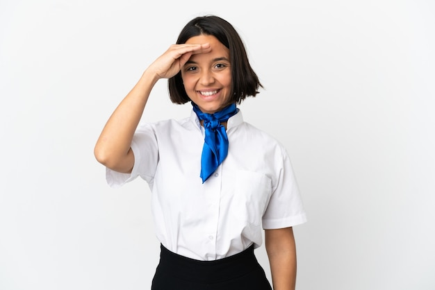 Airplane stewardess over isolated background saluting with hand with happy expression