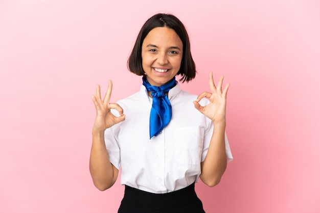 Airplane stewardess over isolated background showing ok sign with two hands