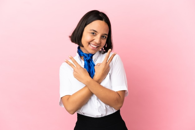 Airplane stewardess over isolated background smiling and showing victory sign