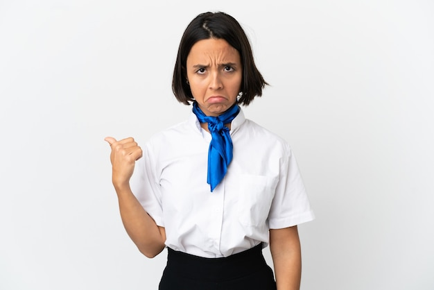 Airplane stewardess over isolated background unhappy and pointing to the side