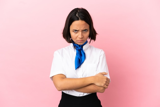 Airplane stewardess over isolated background with unhappy expression