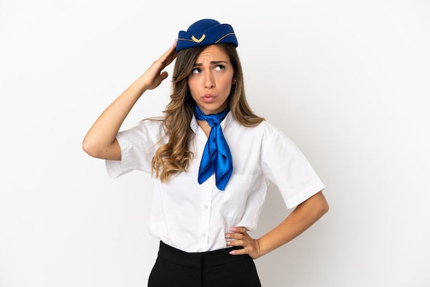 Airplane stewardess over isolated white background having doubts and with confuse face expression