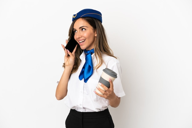 Airplane stewardess over isolated white background holding coffee to take away and a mobile
