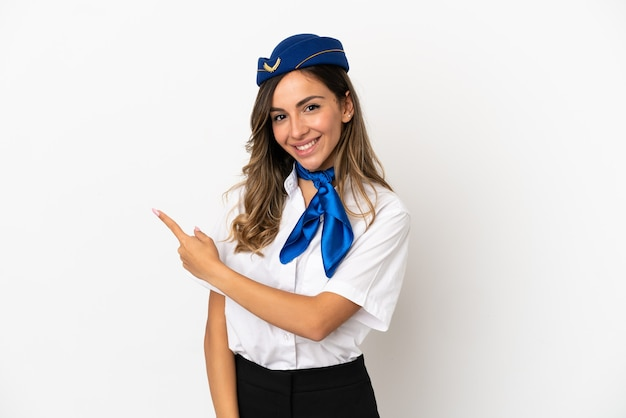 Airplane stewardess over isolated white background pointing to the side to present a product