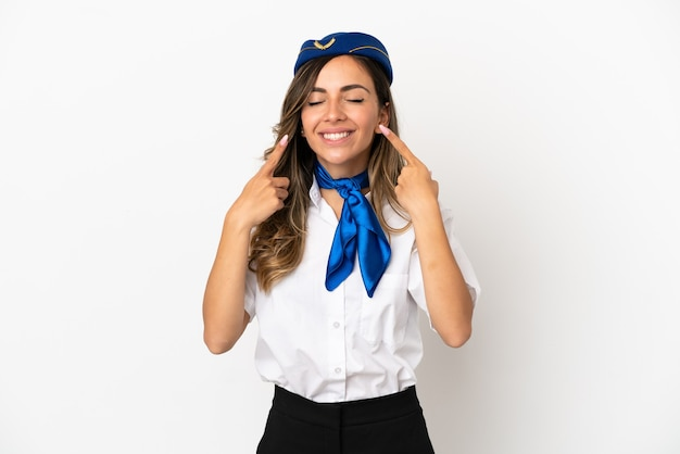 Airplane stewardess over isolated white background smiling with a happy and pleasant expression
