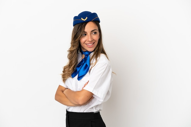 Airplane stewardess over isolated white background with arms crossed and happy