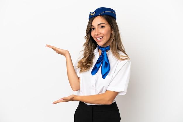 Стюардесса самолета на изолированном белом фоне, протягивая руки в сторону, приглашая приехать