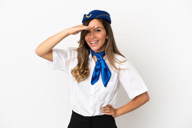 Стюардесса самолета на изолированном белом фоне смотрит вдаль рукой, чтобы что-то посмотреть