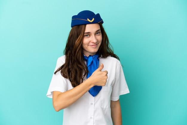 親指を立てるジェスチャーを与える青い背景に分離された飛行機のスチュワーデスの女性