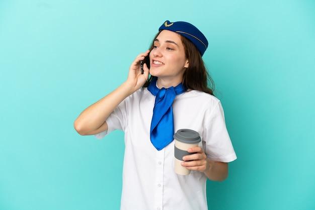 Женщина-стюардесса самолета изолирована на синем фоне, держа кофе на вынос и мобильный