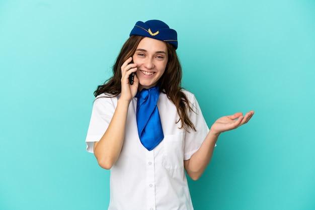 誰かと携帯電話との会話を維持している青い背景に分離された飛行機のスチュワーデスの女性