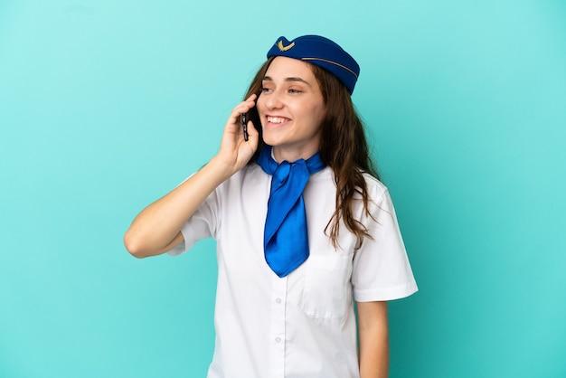 携帯電話との会話を維持している青い背景に分離された飛行機のスチュワーデスの女性