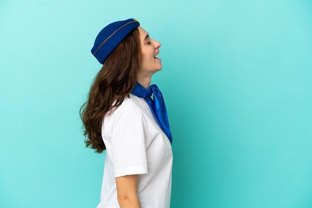 横向きの位置で笑って青い背景に分離された飛行機のスチュワーデスの女性