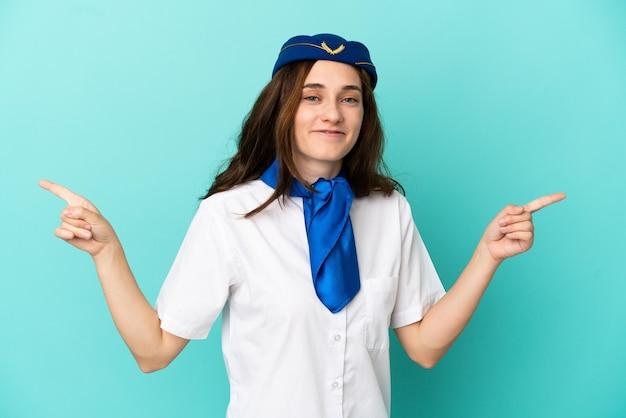 側面に指を指し、幸せな青い背景に分離された飛行機のスチュワーデスの女性