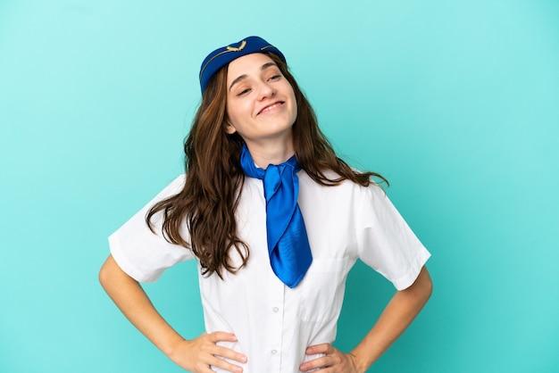 青い背景に分離された飛行機のスチュワーデスの女性が腰に腕と笑顔でポーズをとる