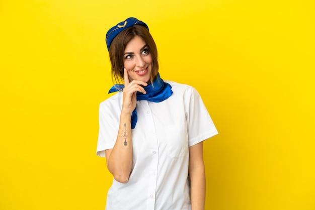 疑いを持って、混乱した表情で黄色の背景に分離された飛行機のスチュワーデスの女性