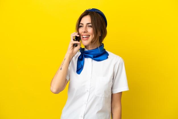 携帯電話との会話を維持黄色の背景に分離された飛行機のスチュワーデスの女性