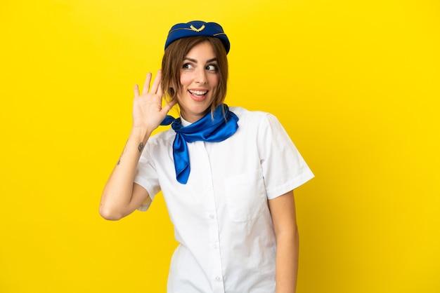 Женщина-стюардесса изолирована на желтом фоне, слушая что-то, положив руку на ухо