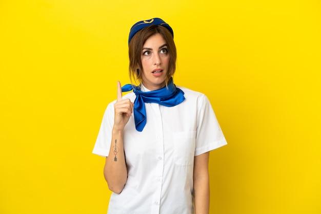 指を上に向けるアイデアを考えて黄色の背景に分離された飛行機のスチュワーデスの女性